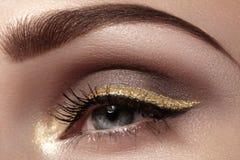 Schöner Makroschuß des weiblichen Auges mit zeremoniellem Make-up Perfekte Form von Augenbrauen, Eyeliner und hübsches Gold zeich Lizenzfreies Stockfoto
