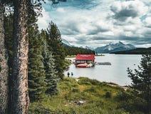Schöner Maligne See mit einem Bootshaus waren Sie kann Kanus und Schnee bedeckte Berge am Hintergrund mieten lizenzfreie stockbilder