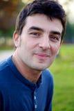 Ernster gutaussehender Mann, der im Park lächelt lizenzfreie stockfotografie