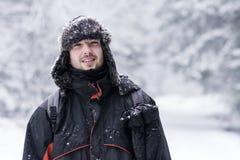 Schöner Mann, der im Winterwald, den Winterschnee genießend einfriert Stockfoto