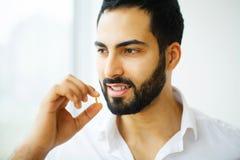 Schöner Mann, der Pille, Medizin einnimmt Vitamine und Ergänzungen stockfotografie