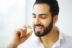 Schöner Mann, der Pille, Medizin einnimmt Vitamine und Ergänzungen lizenzfreie stockfotos