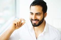 Schöner Mann, der Pille, Medizin einnimmt Vitamine und Ergänzungen stockfoto