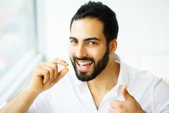 Schöner Mann, der Pille, Medizin einnimmt Vitamine und Ergänzungen stockfotos