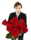 Schöner Mann mit einem Blumenstrauß der Rosen Lizenzfreies Stockbild