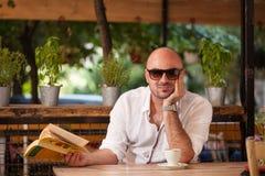Schöner Mann-Morgen-Kaffee mit einem Buch Stockbilder