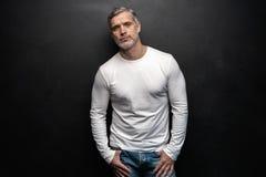 Schöner Mann von mittlerem Alter im weißen T-Shirt, das vor einem schwarzen Hintergrund mit Kopienraum aufwirft stockfoto