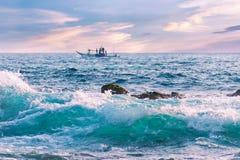 Schöner Meerblick bei Sonnenuntergang, eine Welle mit klarem Wasser, ein Boot mit Fischern auf dem Horizont stockbild