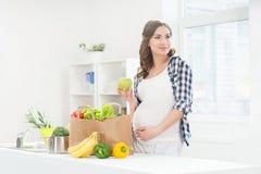 Schöner mischender Salat der schwangeren Frau mit hölzernen Löffeln Lizenzfreie Stockbilder