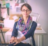Schöner Modedesigner, der am Schreibtisch im Studio sitzt lizenzfreies stockbild