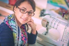 Schöner Modedesigner, der am Schreibtisch im Studio sitzt lizenzfreie stockfotos