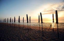 Schöner Morgensonnenaufgang mit Strandsonnenschirm Stockbild