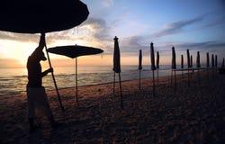 Schöner Morgensonnenaufgang mit Strandsonnenschirm Stockfoto