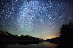 Schöner nächtlicher Himmel, die Milchstraße, Sternspuren und die Bäume Lizenzfreie Stockbilder