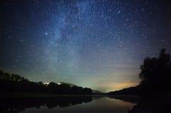 Schöner nächtlicher Himmel, die Milchstraße, Sternspuren und die Bäume Lizenzfreies Stockbild