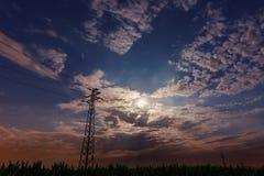 Schöner nächtlicher Himmel, Vollmond, schöne Wolken Freileitungsmaste Stockbild