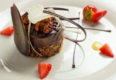 Schöner Nachtisch: Schokoladenkuchen mit Nüssen auf einer Plattennahaufnahme Lizenzfreies Stockbild