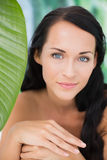 Schöner nackter Brunette, der an der Kamera mit grünem Blatt lächelt Lizenzfreie Stockbilder