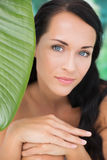 Schöner nackter Brunette, der an der Kamera mit grünem Blatt lächelt Stockbild