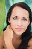 Schöner nackter Brunette, der an der Kamera mit grünem Blatt lächelt Stockfotos