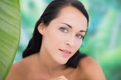 Schöner nackter Brunette, der an der Kamera mit grünem Blatt lächelt Lizenzfreies Stockfoto