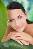 Schöner nackter Brunette, der mit grünen Blättern aufwirft Lizenzfreies Stockfoto