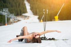 Schöner nackter weiblicher Skifahrer liegt auf schneebedeckter Steigung nahe Skiaufzug am Erholungsort Stockfotografie