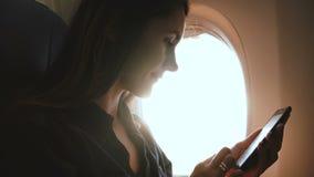 Schöner Nahaufnahmeblendenfleck geschossen von der jungen entspannten Frau, die Smartphonee-commerce App auf Flugzeugfensterplatz stock footage