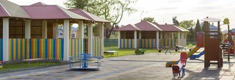 Schöner neuer moderner Spielplatz im Kindergarten mit weicher Pflasterung, helle neue mehrfarbige Nischen, schwingt, Dias, Bänke, lizenzfreie stockfotografie