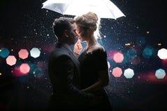 Schöner Paarmann mit Frau mit weißem Regenschirm in den Blitzlichtern und in den Regentropfen Stockbild