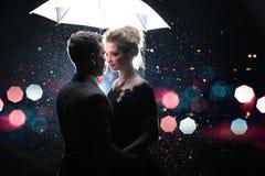 Schöner Paarmann mit Frau mit weißem Regenschirm in den Blitzlichtern und in den Regentropfen Stockbilder