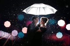 Schöner Paarmann mit Frau mit weißem Regenschirm in den Blitzlichtern und in den Regentropfen stockfoto