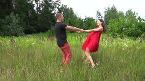 Schöner Paarmann und schwangere Frau mit dem langen Haar in einem roten Kleid familie stock video footage