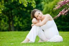 Schöner Park der schwangeren Frau im Frühjahr lizenzfreie stockfotografie