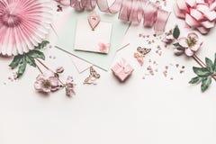 Schöner Pastellrosaplan mit Blumendekorations-, -band-, -herz-, -bogen- und -kartenspott oben auf weißem Schreibtischhintergrund, stockfotos