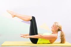 Schöner pilates Lehrer mit gelber Yogamatte Stockbild