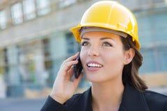 Schöner professioneller junge Frauen-Auftragnehmer-tragender Schutzhelm auf Standort unter Verwendung des Telefons Stockfoto