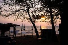Schöner purpurroter Sonnenuntergang auf Pattaya-Strand mit Blick auf die Sonnenbetten und -regenschirme im Schatten stockbild