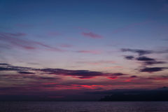 Schöner purpurroter Sonnenuntergang an der Gebirgsküste Stockbilder