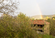 Schöner Regenbogen über einer Hütte im Wald Lizenzfreie Stockbilder
