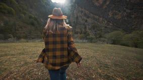 Schöner Reisender der jungen Frau läuft frei über das Feld in der Natur unter den Bergen Wirft einen Hut in die Luft stock video footage