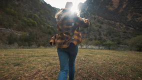 Schöner Reisender der jungen Frau läuft frei über das Feld in der Natur unter den Bergen Wirft einen Hut in die Luft stock video