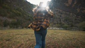 Schöner Reisender der jungen Frau läuft frei über das Feld in der Natur unter den Bergen Wirft einen Hut in die Luft stock footage