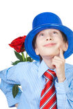 Schöner romantischer Junge, der ein Hemd, eine Bindung und blauen Hut halten eine Rose trägt Lizenzfreies Stockbild
