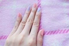 Schöner rosa Nagellack Weibliche Hände mit rosa Nagel-Maniküre auf rosa Gewebe-Hintergrund lizenzfreie stockfotografie