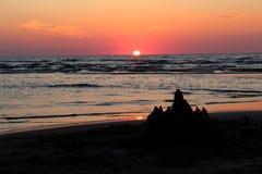 Schöner rosa Sonnenuntergang mit einer Sonnenbahn und einem Sandburg im Vordergrund Stockfotografie
