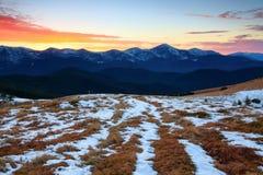 Schöner rosa Sonnenuntergangglanz erleuchtet die malerischen Landschaften mit angemessenem gelbem Gras und Hochgebirge stockbilder