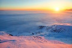 Schöner rosa Sonnenuntergangglanz erleuchtet die malerischen Landschaften mit den angemessenen Bäumen, die mit Schnee und Hochgeb stockfotografie