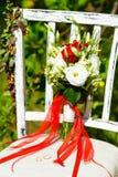 Schöner roter Brautblumenstrauß steht auf einem Stuhl im Park Stockbilder