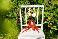 Schöner roter Brautblumenstrauß steht auf einem Stuhl im Park Stockbild